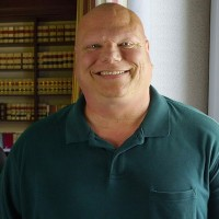 Smiling bald man in a law library