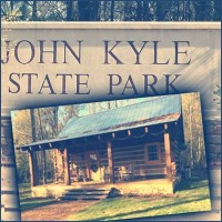 Rustic cabin in front of a sign for John Kyle State Park