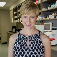 Woman with a blonde pixie haircut in a pharmacy