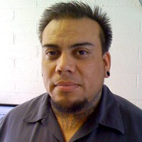 Man with short, spiky dark hair, a goatee, and neck tattoos