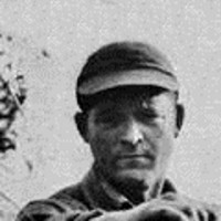 Old photo of an unsmiling man in a baseball cap