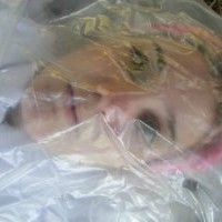 Pink-haired young woman wrapped in clear plastic
