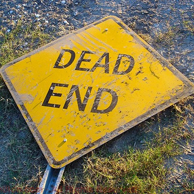 Dead End street sign lying on the ground