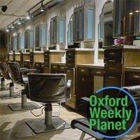 A row of stylist chairs in front of mirrors in a hair salon with the Oxford Weekly Planet logo in the foreground