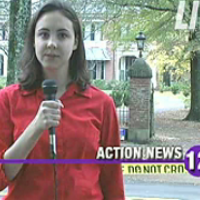 TV reporter standing in front of crime scene tape blocking the entrance to a mansion