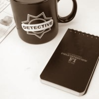 Detective's mug and notebook with a fingerprint card in the background