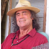 Man with long dark hair wearing a straw hat and red shirt