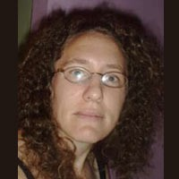 Woman with long dark curly hair and glasses