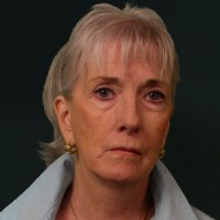 Middle-aged woman with light hair and a sad expression