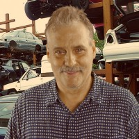 Man with light brown hair and a salt-and-pepper mustache standing in front of an auto yard