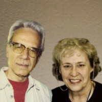 Man with gray hair & glasses and smiling woman with blonde hair