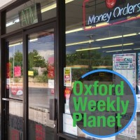 Convenience store entrance with Oxford Weekly Planet logo in the foreground of the bottom right corner