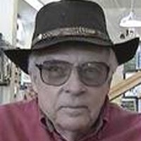 Unsmiling older man with a cowboy hat and tinted glasses