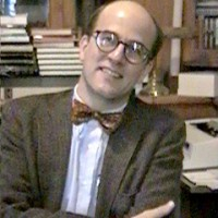 Balding man in his mid-40s wearing a tweed blazer and a bow tie