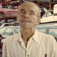 Man with a salt-and-pepper mustache and thinning hair, standing in front of an auto yard