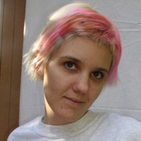 Young woman with short blonde hair and pink highlights