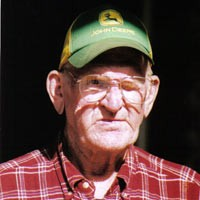 Elderly man with glasses, a green trucker hat, and a red plaid shirt