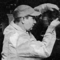 Old photo of a man in a baseball cap reaching for something on a shelf
