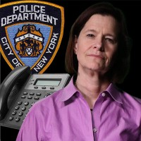 Woman with dark hair in front of business telephone and an NYPD seal