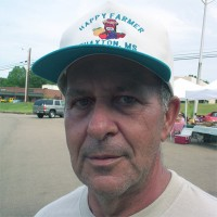 Man with salt-and-pepper hair and five o'clock shadow, wearing a t-shirt and trucker hat
