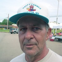 Man with gray hair and five o'clock shadow in a trucker hat