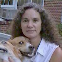Woman with long dark curly hair pictured with two dogs