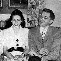 Old photo of a dapper, dark-haired man seated next to a dark-haired woman