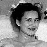 Smiling, dark-haired woman in a bathtub