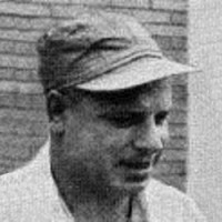 Old photo of a smiling man in a baseball cap