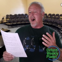 Man singing in an empty choral rehearsal room