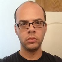 Unsmiling balding man with glasses