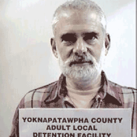 Older man with white hair, mustache and beard holding a jail booking card