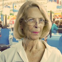 Older woman with blonde hair, glasses, and bright pink lipstick