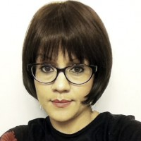 Woman with a short, dark bob and dark-rimmed glasses