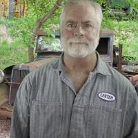 Man with gray hair and beard, wearing coveralls and standing in front of a rusted antique vehicle