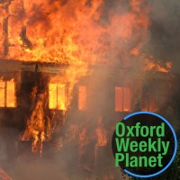 A residence engulfed in flames with the Oxford Weekly Planet logo in the foreground