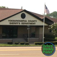 Exterior of the Yoknapatawpha County Sheriff's Dept. office with the Oxford Weekly Planet logo superimposed in the lower right corner