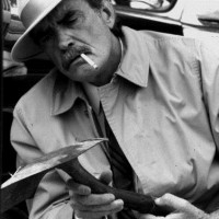 Man wearing a hat and raincoat and smoking a cigarette while examining a shovel