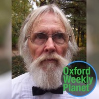 Man with glasses and white hair, beard and mustache with the Oxford Weekly Planet logo in the foreground