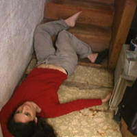Woman lying at the bottom of a staircase