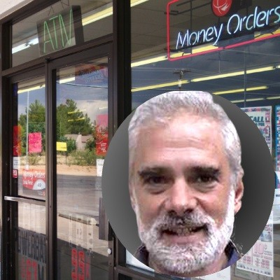 Convenience store entrance with photo inset of an older man with white hair, mustache and beard
