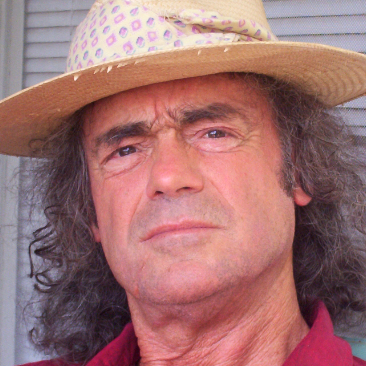 Man with long dark hair wearing a red shirt and a straw hat