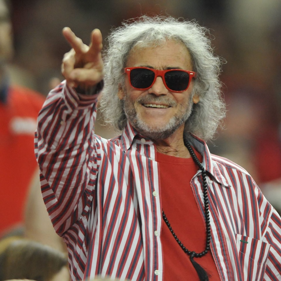 Man with long white hair wearing a red striped shirt and sunglasses