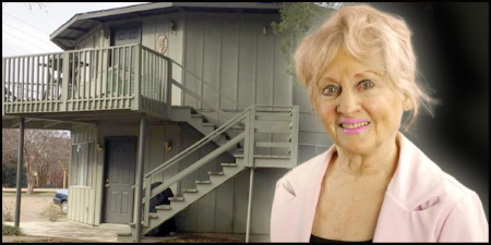 An older woman with blonde hair in front of an apartment building