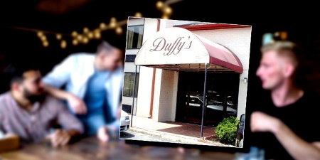 People chatting at a table in a bar with a photo of the Duffy's Bar & Grill entrance in the foreground