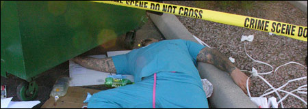 Man lying dead next to a dumpster