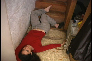 Woman's body on the floor at the bottom of the stairs