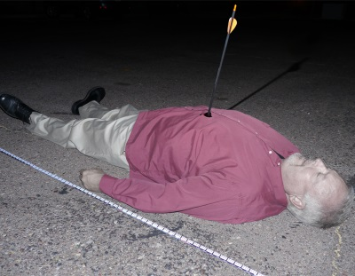 Man lying on his back on the asphalt with an arrow sticking out of his chest