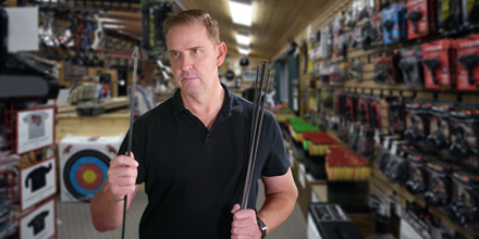 Man holding hunting arrows, standing in a sporting good store
