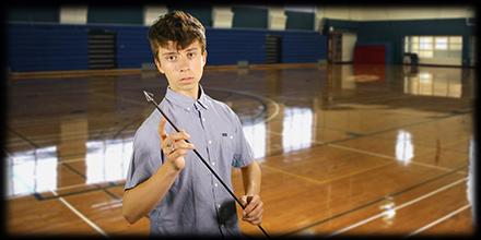 Teen boy holding an arrow, standing on an empty basketball court